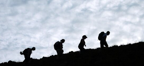 4 persons walk up a mountain