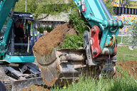 Finance Minister of Saxony Prof. Georg Unland uses an excavator to turn the firs