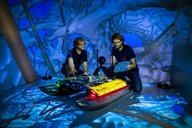 Two men at a swimming robot in the CAVE
