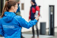 female student holding a smartphone wearing a blue jacket